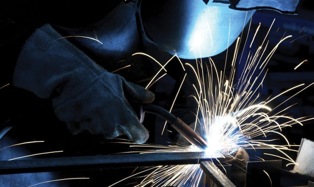 welder in hood and gloves welding with sparks flying