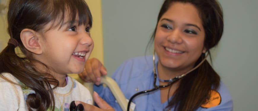 Female nursing student listening to child's heartbeat