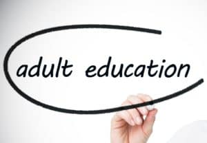 hand writing adult education on whiteboard