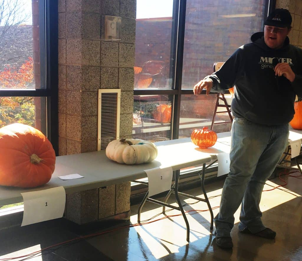 Male student talking in front of table with 3 pumpkins