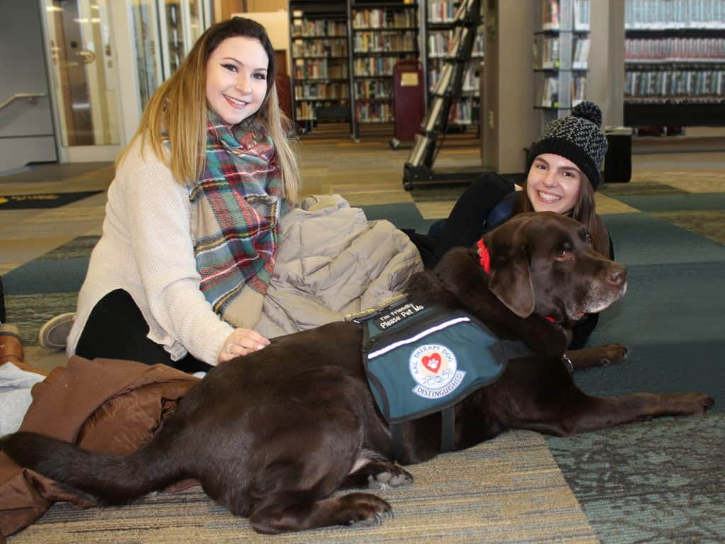 two female students with brown English lab dog