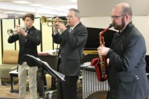 3 members of Black Hawk College Jazz Band playing trumpets and alto sax