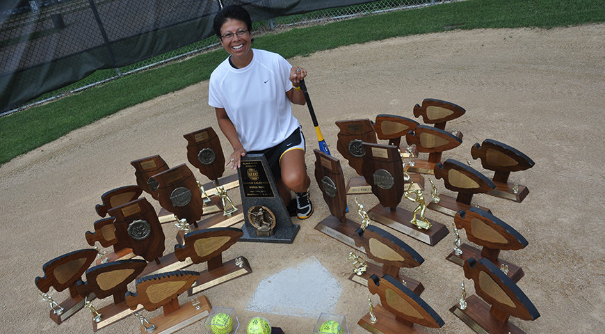 Coach Carrie Calderon with many trophies on the softball field