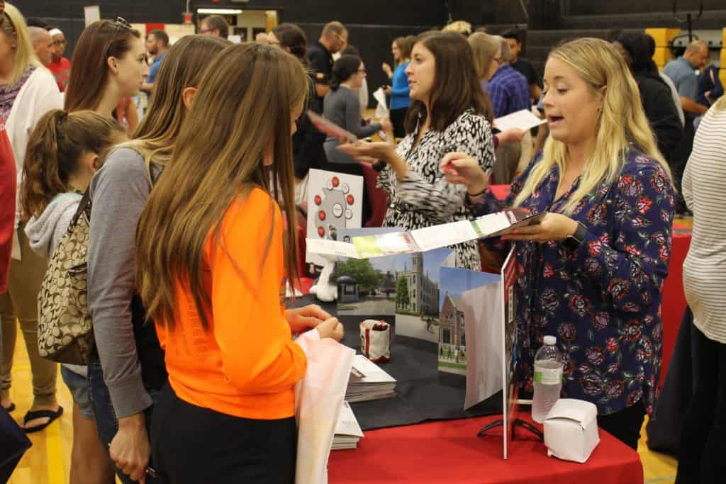 Female recruiter talking with mom & daughter at College Night 2017