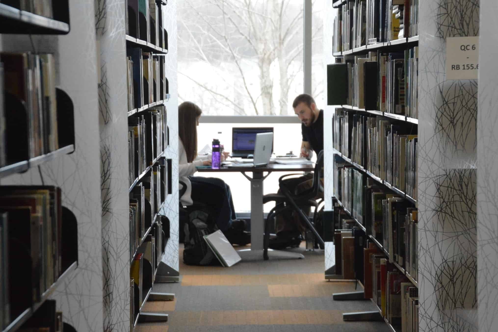 two students studying at table in QC Library 3-9-16