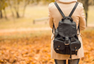 female student with back to camera wearing backpack in autumn park
