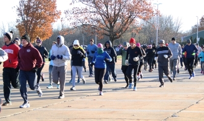 Runners bundled up running through parking lot
