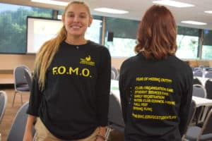 two Student Government Association members wearing Free of Missing Out t-shirts