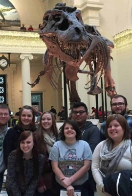 students at the Field Museum in front of a T-rex skeleton