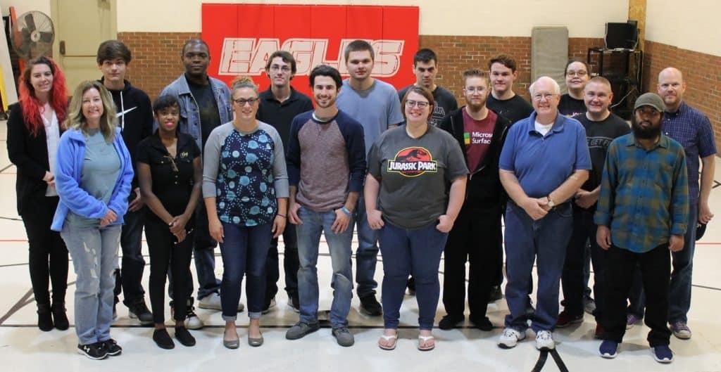 15 students & instructors standing in school gym