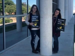 two female college students holding Black Hawk College signs