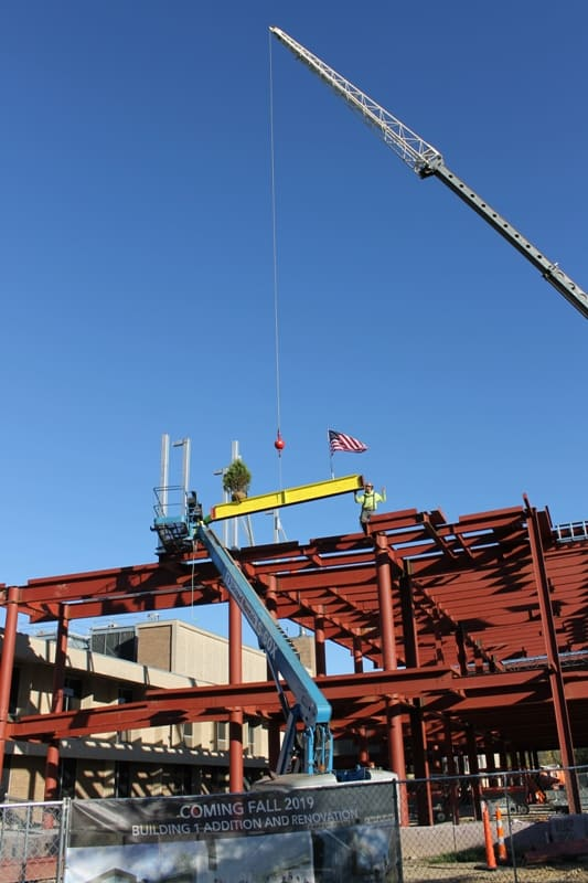 crane lowers yellow beam with evergreen & American flag down to worker on top of red steel framework of new 2-story building