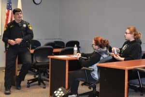 Black Hawk College Police Corporal presenting to a group of students sitting at desks