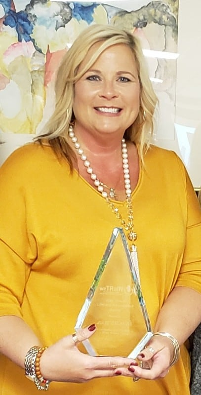 smiling woman in yellow shirt holding triangular acrylic award