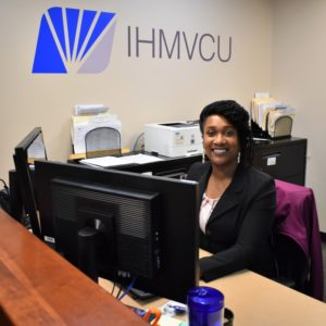 """BHC graduate Tamica Reynolds sitting at desk with sign behind her """"IHMVCU"""""""