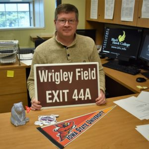 """Dale Huntley sitting at his desk holding sign saying """"Wrigley Field EXIT 44A"""" with a flag in front of him saying """"Iowa state university"""""""