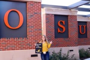 """Grayson Cottrell standing in front of Oklahoma State University building, holding sign that says """"BHC got me here"""""""