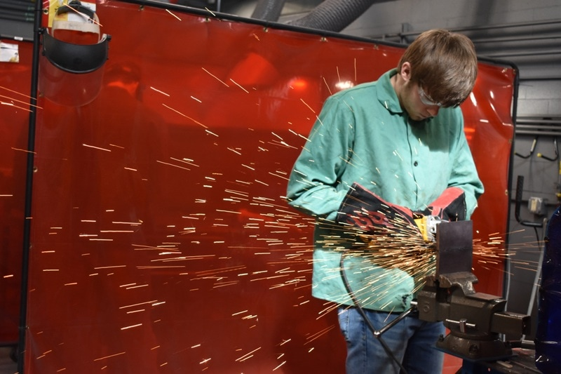 high school student welding with sparks flying