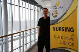 Ian Hutto standing next to yellow BHC nursing sign, next to windows