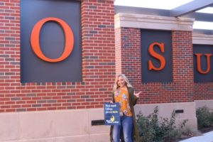 "Ryleigh Semanchik standing in front of Oklahoma State University building, holding sign that says ""BHC got me here"""