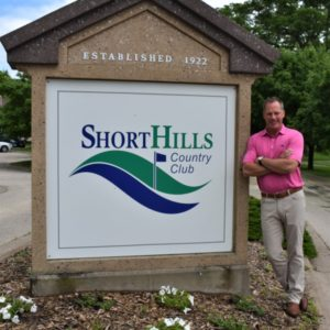 BHC alumnus Mike Downing standing next to Short Hills Country Club sign outside