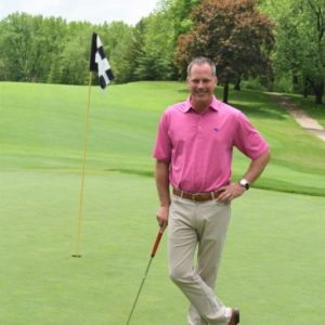 BHC alumnus Mike Downing standing in golf course, next to a flag