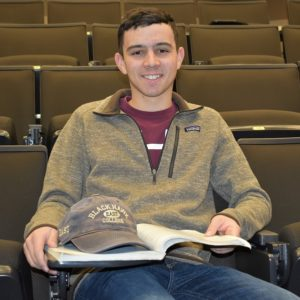 student sitting in theater room with book open on lap and hat resting on book