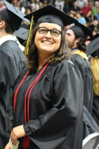 smiling female grad wearing glasses and red cords