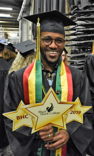 """Amadou Ndiaye wearing graduation gown. Holding 3 signs shaped like gold stars saying """"BHC"""", """"Black Hawk College"""", and """"2019"""""""
