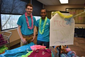 "two students standing next to sign that says ""free t-shirts"" and a table covered with t-shirts"
