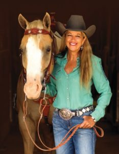 woman wearing cowboy hat standing with horse