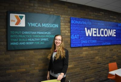 woman in front of brick wall with YMCA mission and welcome signs