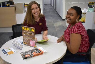 Financial Aid director and student sitting at a table smiling
