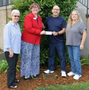 4 people standing outdoors with a check