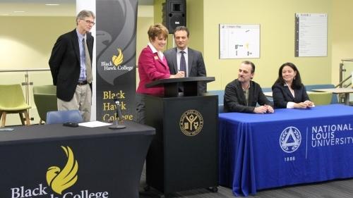 people at podium signing agreement