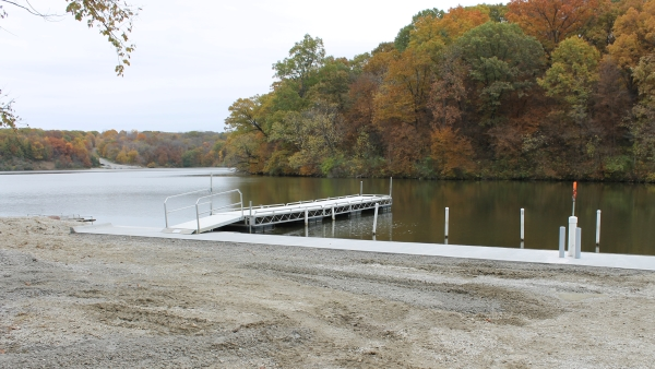 shore, dock and lake with colorful fall trees in background