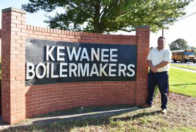 teacher standing next to a brick Kewanee Boilermakers sign with a school bus in the background