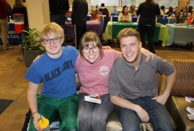 three smiling students sitting on a couch with information booths in the background