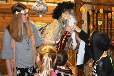 student and horse dressed in disco costumes with kids in costume petting the horse