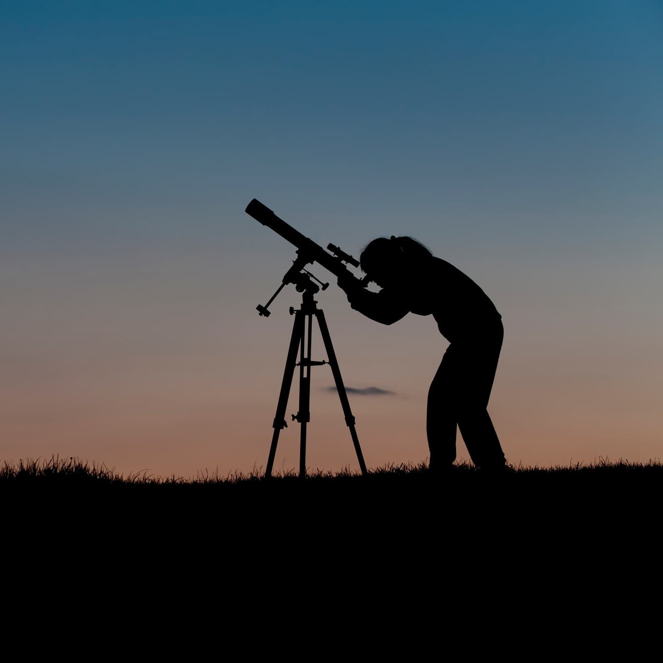 person looking into telescope at night