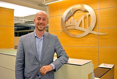 man in suit in front of a desk with a Q-shaped logo on the wall featuring a cityscape