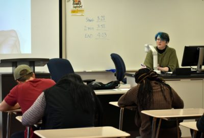 students sitting at desks while an assistant professor teaches