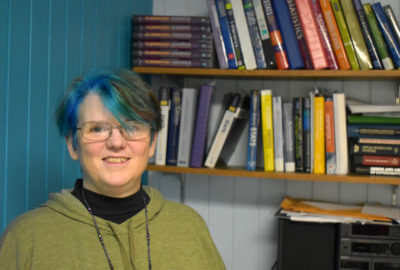 smiling instructor in office with shelves filled with math books behind her