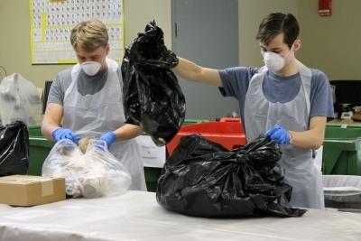 2 people sorting through bags of trash