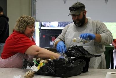 2 people sorting through bag of trash