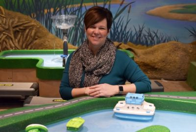 woman leans on a water play table with floating boats in front of her