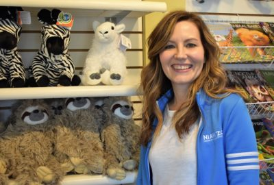 woman standing in front of a display of stuffed animals and books