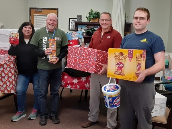 4 people holding food & candy donations