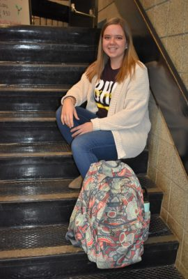 female student sitting on stairs with book bag in front of her