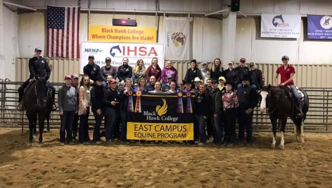 group of equine students in arena with banner, award ribbons & 2 horses